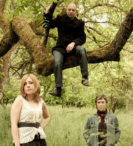 the members of the Corin Tucker Band hang out in a grassy field. The sky is grey.