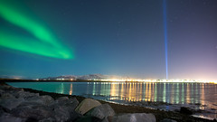 Northern lights over Reykjavik iceland and Imagine Peace Tower (Arnar Bergur) Tags: blue sea sky color green stars island lights iceland rocks stones reykjavik shore aurora sland northernlights borealis canoneos5d canon24mm14l imaginepeacetower