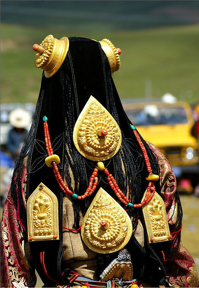 Ornate, massive, pure gold ornaments worn by bejewelled girl at Lithang Horse Festival