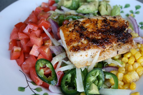 plate of diced tomatoes, avocado, corn, red onions, and jalapeno peppers with a piece of blackened fish on top