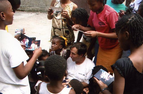 Image of Jeff Behringer with Haitian children, whom he supports with profits from Behringer Stone Company and with his expertise in building and repairing masonry