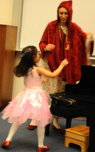 The Piano Recital, A pink fairy and Little Red Riding Hood both wearing red shoes, piano, step stool, University of Alaska Arts building, Anchorage, Alaska, USA by Wonderlane