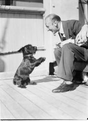 """On the ship """"Mongolia"""": Chuck Arnold and """"Jockey"""" (dog), ca. 1930's / photographer Sam Hood"""