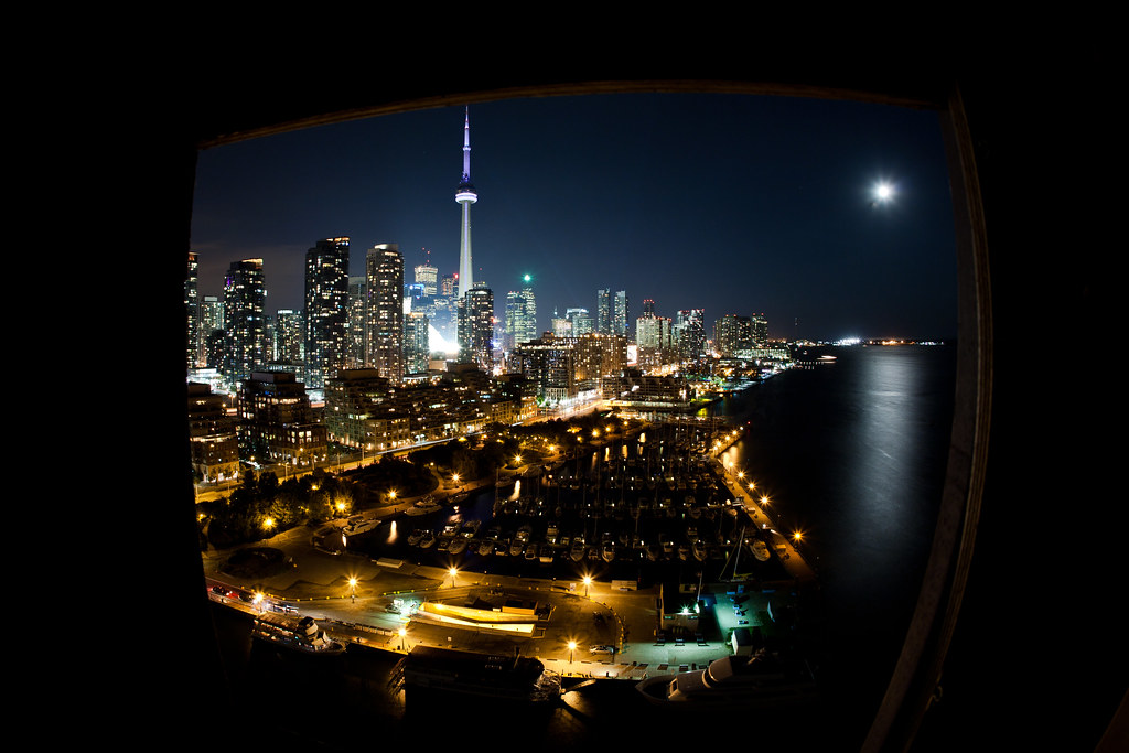 toronto skyline at night with a fisheye through a window at the canada malting co. ltd. plant