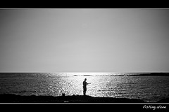 fishing alone (Eric 5D Mark III) Tags: ocean light people bw sun man reflection water monochrome silhouette contrast blackwhite fishing fisherman mood afternoon atmosphere simplicity orangecounty minimalism alisobeach ef1635mmf28liiusm