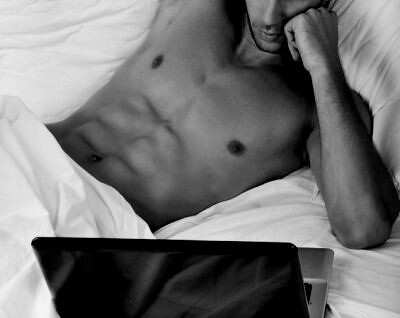 Handsome man lying on the bed, reading a laptop