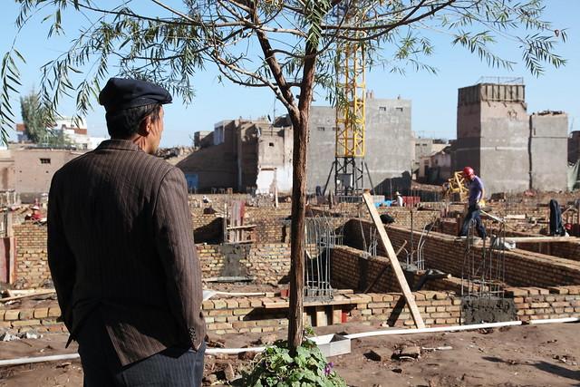 カシュガル旧市街、取り壊し後の新築現場を見つめる男性