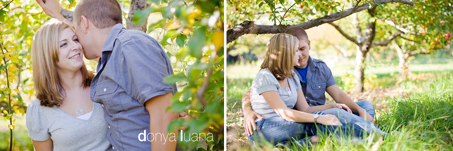 Sweet couple snuggle under apple tree in southern minnesota for engagement photos