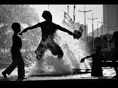 Farra com o surfista (De Santis) Tags: shadow brazil white black água branco brasil ball nikon child play chafariz sombra preto sp santos font bola crianças fonte d3000 tpasilhouette