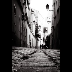 in restless dreams i walked alone (helen sotiriadis) Tags: street bw white paris france monochrome architecture canon back published pov low perspective montmartre cobblestone pointofview narrow canonef50mmf14usm canoneos40d