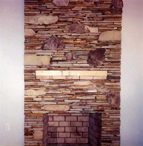 fireplace built with stone in a style that places a few stones upright and all surrounding stones flat and horizontal