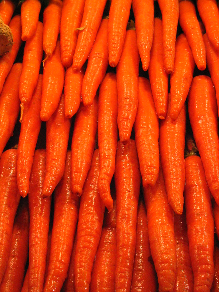 Rows of glistening wet carrots at a vegetable stand
