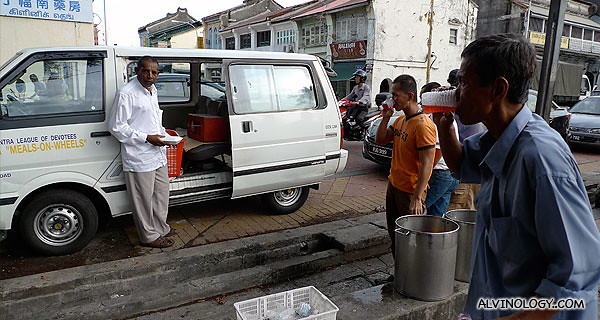 """""""Meals on Wheels"""" - free food given out outside the Goddess of Mercy temple, besides an Indian shrine"""