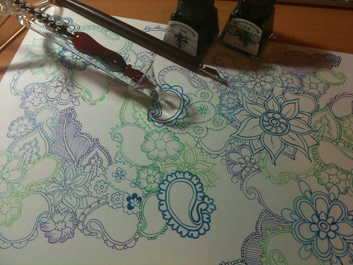 Photo of  a drawing of paisley in different coloured inks (blues and greens). Two small bottles of ink, a glass dip pen and a wooden dip pen with a metal nib sit on top of the paper.