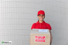 delivery courier with  package. copy space (mauricio jordan) Tags: red portrait people woman man black girl smile smiling wall work outside outdoors happy person grey one uniform looking mail box labor working teen cardboard cap transportation latin distributed friendly delivery carton service worker postal hispanic copyspace parcel shipping courier job package fragile freight deliver teenage postman 20s delivering isyndica