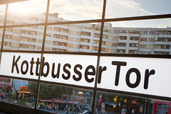 Kott|busse|r Tor (dmoch) Tags: light summer sky sun berlin window glass station sign clouds train kreuzberg germany subway glow afternoon letters ubahn typo kotti sunflare appartmenthouse kottbussertor xberg pentaxk10d pentaxda1645mmf4