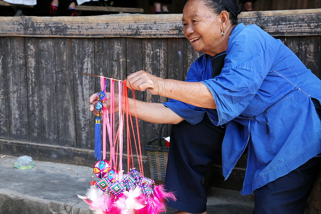 A woman selling gifts to tourists in Chengyang, Guangxi, China