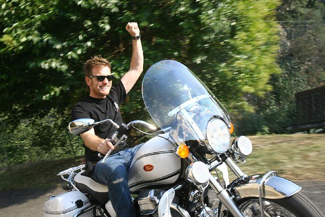 Ewan Mcgregor rides motorbike like a real man.