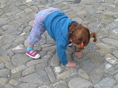 Speck, hair in two pigtails, walking on all fours on cobblestones