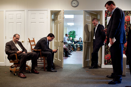 President Barack Obama answers questions about the economy from local families as, from left, Senior Advisor David Axelrod, Deputy Press Secretary Bill Burton, Director of Speechwriting Jon Favreau, and Trip Director Marvin Nicholson wait in a hallway of the Southhampton Recreation Association in Richmond, Va., Sept. 29, 2010. (Official White House Photo by Pete Souza)