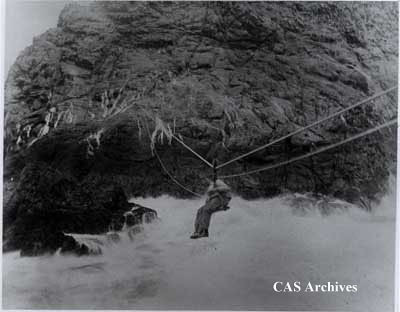 """Eggers trolley to Sea Island Islet."" South Farallon Island, July '96. Man sitting on trolley off side of rock."