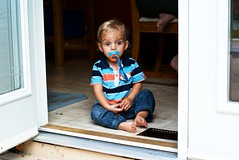 cooped|up (DJHuber) Tags: door blue baby feet shirt yard back kid eyes backyard toddler sitting child play floor marcus bare patio jeans sit striped soother