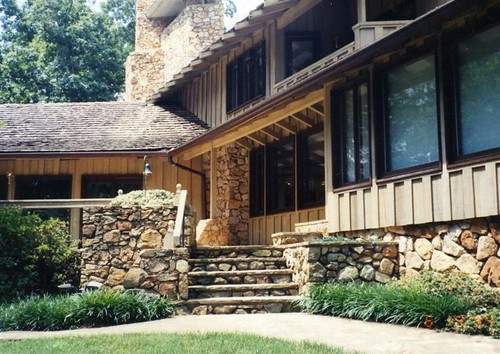 flagstone patio surrounded by short stone walls and larger walls of the garage and main house