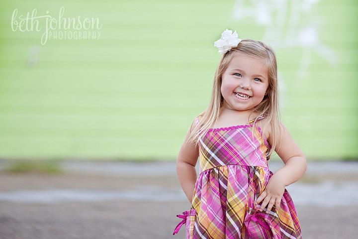 three year old girl in front of green garage door
