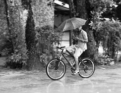 Biking in the rain, par Franck Vervial (Franck Vervial) Tags: street people rain bike bicycle umbrella blackwhite seychelles ladigue