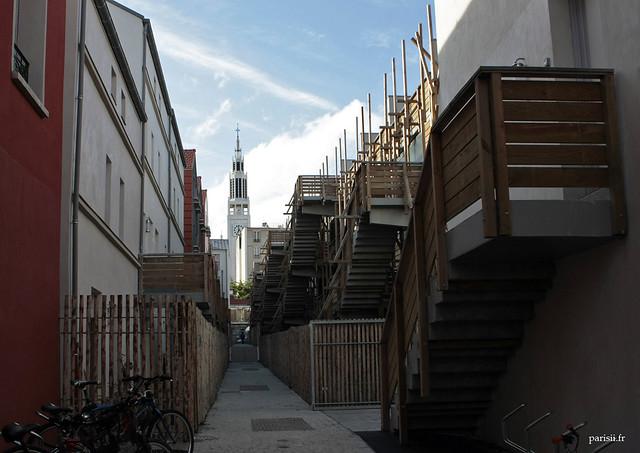 On aperçoit au fond de cette petite rue refaite l'église Saint Jean-Bosco