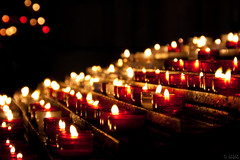 Prayers (Ronel Reyes) Tags: travel light red church digital canon eos lights europe candles cotedazur dof darkness cathedral photos bokeh flames montecarlo monaco indoors candlelight xs frenchriviera 1000d