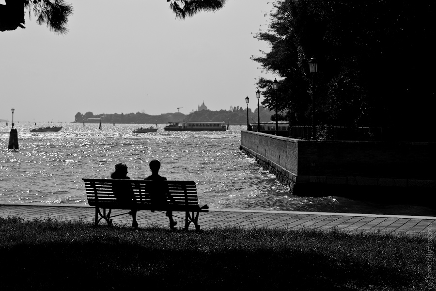 Two people sitting on a bench in Venice, Italy
