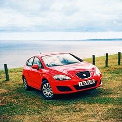 Shiny New Car (slimmer_jimmer) Tags: sea sky tlr car mediumformat xpro crossprocessed cliffs crossprocessing newcar redcar seatleon yashica635 durdledor