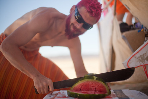 Man chopping watermelon with a machete