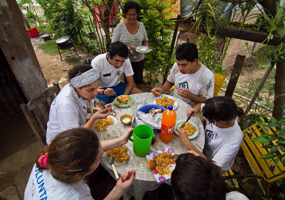 Los voluntarios almuerzan despues de una ardua jornada de trabajo, los beneficiarios de las viviendas recibían alimentos para preparar el almuerzo a los constructores. (Tetsu Espósito - Lambaré, Paraguay)
