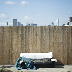 room with a view. (Vitaliy P.) Tags: street new york city nyc blue light sky sun sunlight building tower water skyline clouds fence square outside outdoors island wooden bed weeds nikon long natural manhattan homeless sheets couch explore sidewalk queens un crop blanket 60mm sunnyside f28 juxtapose explored d80 vitaliyp gettysubmitted