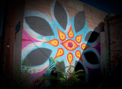 graffiti of big, multicolored flower mandala with eye at the center