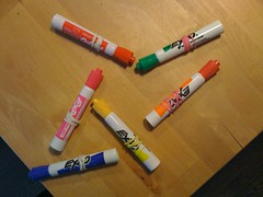 Colored markers, each with a rubber band wrapped around it.