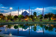 The Blue Mosque at dusk (modenadude) Tags: blue trees sky cloud sun 3 reflection green water fountain beautiful rain set night canon turkey lights is cloudy dusk minaret muslim islam prayer dramatic istanbul mosque tiles adobe dome serene sultan ottoman usm ahmed f28 thunder hdr masjid sultanahmet lightroom camii 1755mm photomatix 550d thunderstom t2i