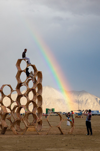 A hexagonal wooden structure with some people on and around it, a rainbow in the background.