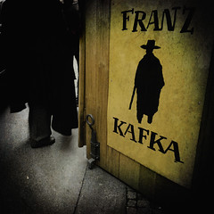 Behind K. (Sator Arepo) Tags: door leica urban hat silhouette czech prague coat praha praga walker kafka franzkafka zuiko trial mistery digilux 714mm digilux3