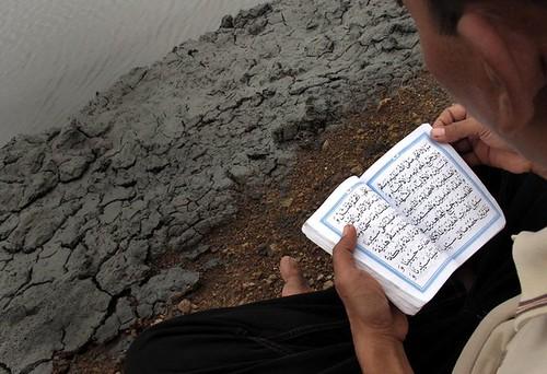 TABUR BUNGA. Seorang warga korban lumpur panas Lapindo, membaca doa sesaat