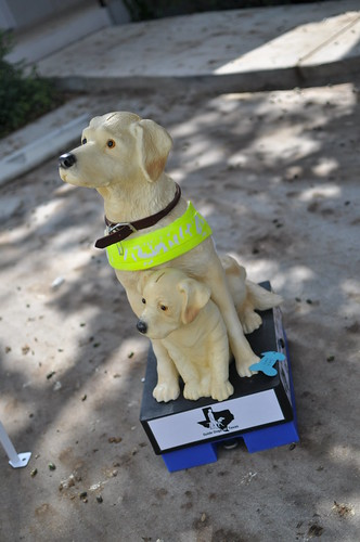 picture of a plastic guide dog with a puppy at her feet, it is a giant piggy bank for people to donate into