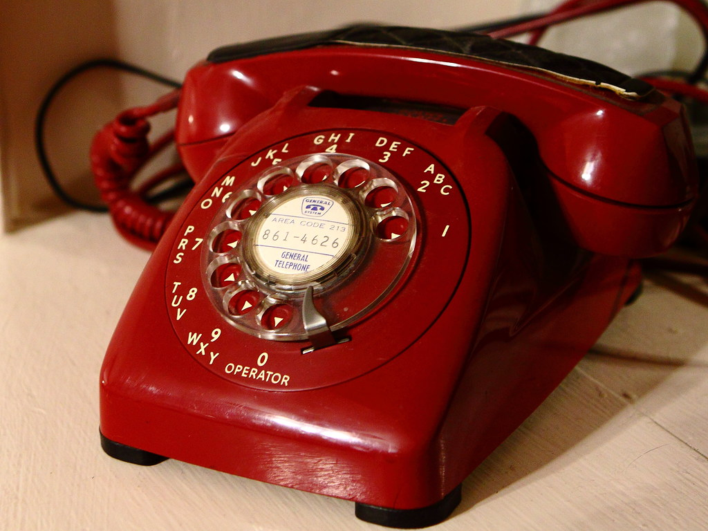 Old red rotary dial telephone