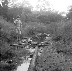 The foul and stinky Swamp Canal behind the Woodmont Pumping Station and a significantly younger me examining some choice tidbit found in the muck. Milford Connecticut. Aug 1973 (wavz13) Tags: family friends blackandwhite bw trash vintage garbage kodak memories oldschool litter pollution disgusting 1970s smelly instamatic teenage panchromatic 126film 126instamatic vintageconnecticut oldconnecticut 1970sconnecticut
