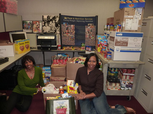 Angela Jones and Michelle Stewart with part of the donations collected by the Midwest Regional Office for the Feds, Farmers, and Friends Feed Families food drive.