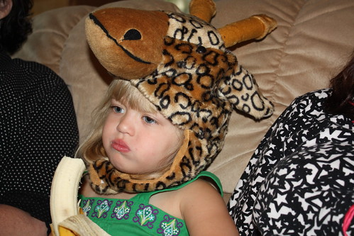 Watching a movie, eating a banana, wearing a giraffe hat.