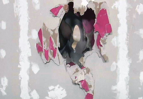 A picture of a hole in a grey wall. The edges of the hole are pink and you can see a high-heeled shoe and black nylons through the hole, they are kicking through the wall.
