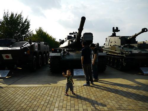 戦車の前でポーズをとる石丸ジュニア