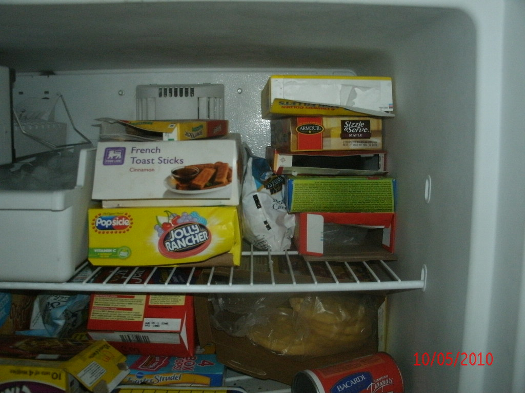 Open boxes of food in freezer in apartment